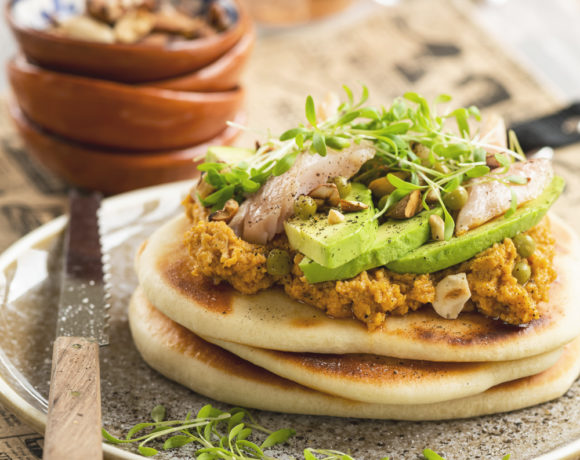 Naan bread with sweet potato spread, trout, avocado, hazelnuts, peas, and garden cress
