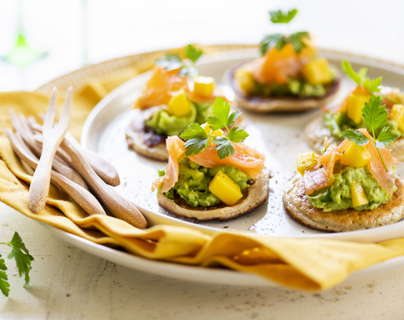 Blinis with homemade avocado cream, smoked salmon and mango
