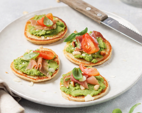 Blinis with pea pesto, Parmesan cheese shavings, pine nuts, and Italian ham